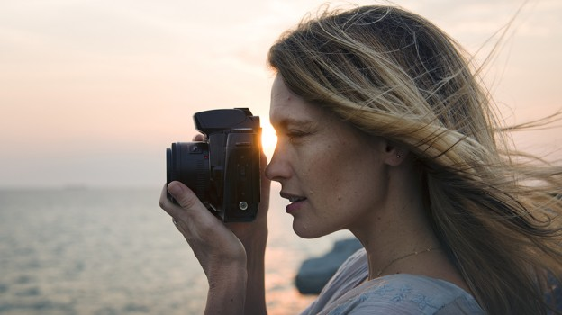 Woman with camera shooting on the beach